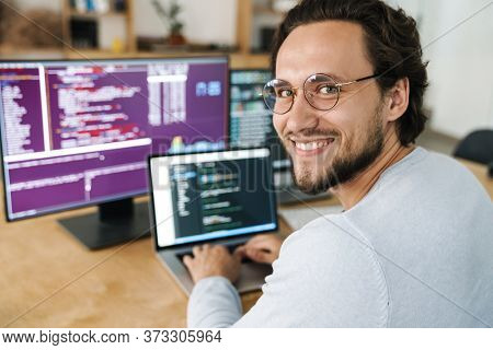 Image of cheerful caucasian programmer man wearing eyeglasses working with computers in office