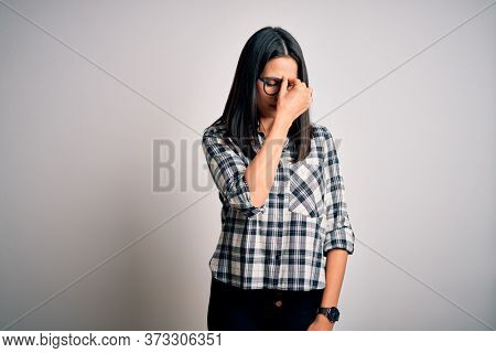 Young brunette woman with blue eyes wearing casual shirt and glasses over white background tired rubbing nose and eyes feeling fatigue and headache. Stress and frustration concept.