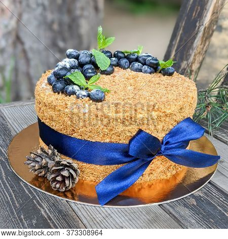Layer Cake Napoleon With Berries Of Blueberry On A Rough Wooden Backgound Sprinkled With Powdered Su
