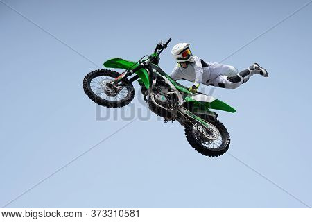 Racer In A White Protective Uniform And Helmet Shares A Stunt In The Air On A Motorcycle
