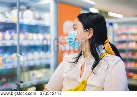 Grocery Shopping During Covid-19. Woman Wearing A Protective Face Mask And Looking At The Dairy Sect
