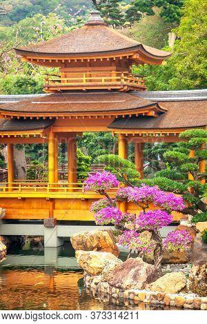 Traditional Chinese Arch, Lake, Stone And Bonsai In Nan Lian Garden, Chi Lin Nunnery, Hong Kong