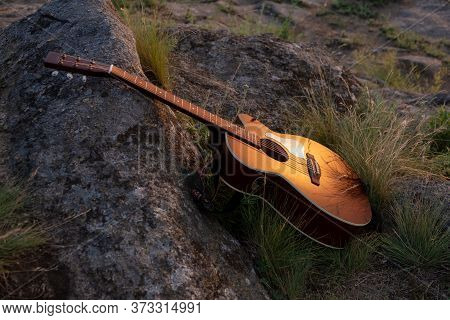 Guitar On The Rock. Acoustic Guitar Outdoor Guitar At The Sunset, Music Background Concept