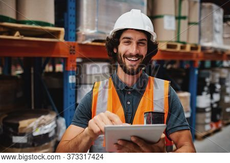 Handsome Cheerful Young Caucasian Smiling Supervisor With White Helmet Using Digital Tablet For Work