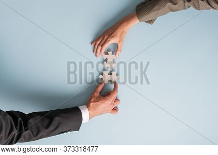 Hands Of A Businessman And Businesswoman Joining Two Puzzle Pieces In A Conceptual Image Of Merger A