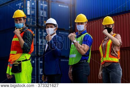 Industrial Workers Or Engineers Wearing Coronavirus Or Covid-19 Protective Masks Join Hands And Stan