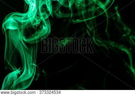 Green Colored Puffed Smoke In A Dark Background