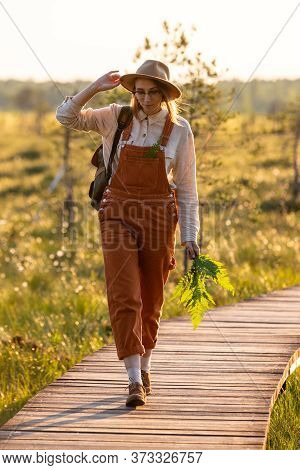 Woman Botanist With Backpack On Ecological Hiking Trail In Summer Outdoors. Naturalist Exploring Wil