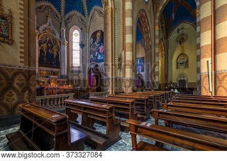 ALBA, ITALY - JUNE 14, 2020: Wooden pews along altars and columns inside of San Lorenzo - a Roman Catholic cathedral aka Duomo dedicated to Saint Lawrence in small town of Alba in Piedmont, Italy.