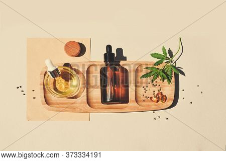 Cbd Oil, Tincture With Marijuana Leaves On A Beige Background. Cannabis Seeds In A Wooden Spoon. Med
