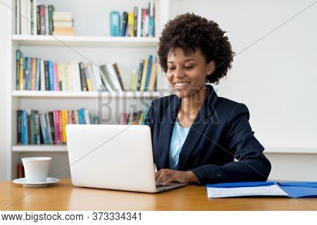 Laughing African American Business Trainee Working At Computer Indoors At Home Or At Office