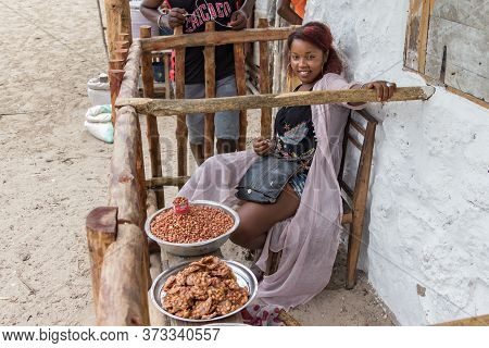 Andavadoaka, Madagascar - January 13th, 2019: Malagasy Woman Selling Dry Fruits Placed On Wooden Tab