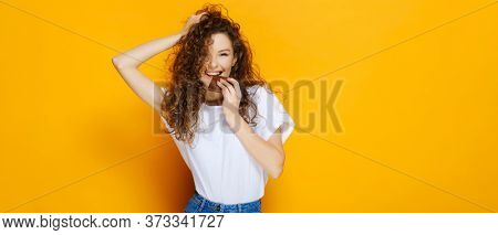 Happy girl with chocolate bar and pretty smile. Model have dental braces for orthodontic treatment with white teeth. Closeup portrait with isolated on yellow background caucasian female and copy space
