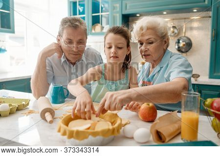Girl And Granny Baking A Pie, Putting Apple Slices Onto Dough