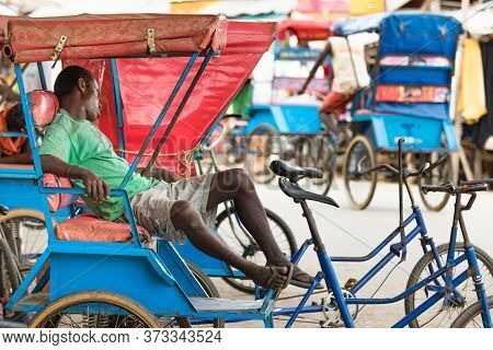Toliara, Madagascar - January 10th, 2019: A Male Malagasy Pousse Pousse Driver Taking A Nap Outdoors