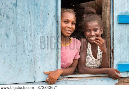 Andavadoaka, Madagascar - January 13th, 2019: Two Local Malagasy Girls Looking Out Of A Window In Th