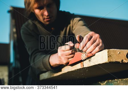 Man woodworker carpenter working with a hand plane. Planing a board is flying shavings. Master manua