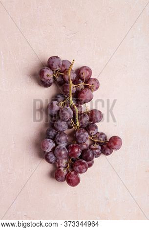 Branch Of Dark Red Grape On Pink Concrete Background. Top View, Flat Lay, Concept Of Sweet Ingredien