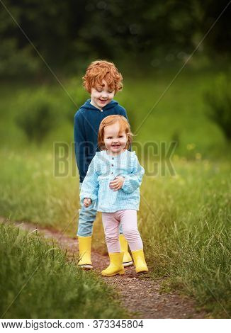 Adorable Smiling Redhead Siblings On The Walk On A Green Meadow