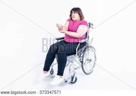 Portrait Images, Asian Fat Woman Sitting On A Wheelchair His Hands Are Kinking Due To A Nervous Syst