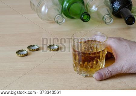 The Social Problem Of Home Alcoholism Concept. Male Hand Holds A Glass With Beer On The Background O