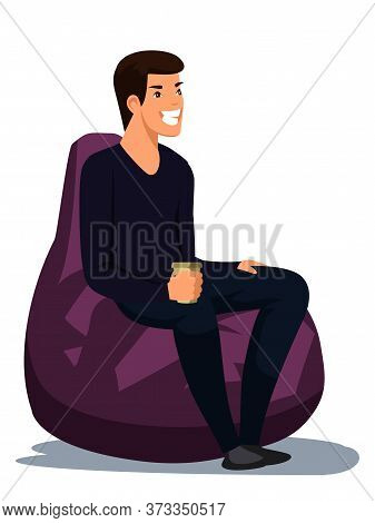 Smiling Happy Man Sitting And Drinking With Takeaway Coffee Cup. Male Character In Soft Bag Chair Is