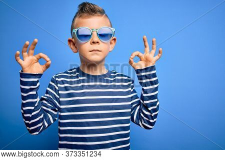 Young little caucasian kid with blue eyes standing wearing sunglasses over blue background relax and smiling with eyes closed doing meditation gesture with fingers. Yoga concept.