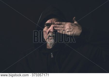 Portrait Of A Man Wearing A Hoodie, Holding One Hand In Front Of An Eye