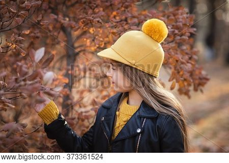 Young Teen Girl With Long Blond Hair In Yellow Sweater, Hat And Leather Jacket Posing In The Autumn