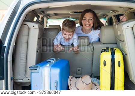 Happy European Woman With Her Little Son Look Back At The Trunk Of A Car With Suitcases. Family Summ