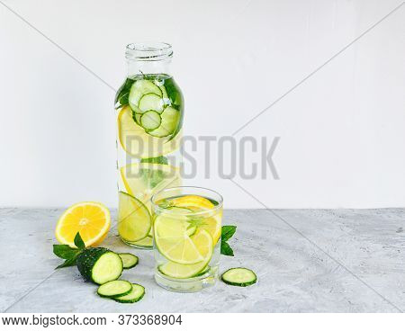A Refreshing Drink Of Lemon, Mint, Cucumber In A Glass Bottle And A Glass. Sassy Diet Water. The Con