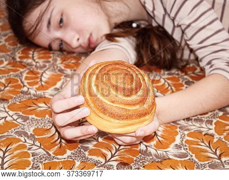 A Teenage Girl Is Lying On The Floor With A Bun In Her Hands. Close-up, Selective Shot, Focus On The