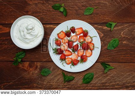 Red Ripe Strawberry Berries Whole And Cut In Half In A White Plate With Whipped Cream In A Bowl Next