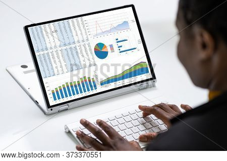 African Business Advisor Using Financial Kpi Dashboard On Laptop