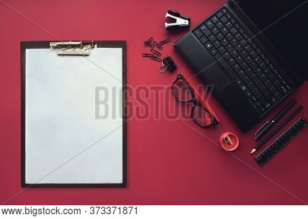Set Of Black Stationery Elements With Plastic Tablet And White Sheet Of Paper On The Red Background.
