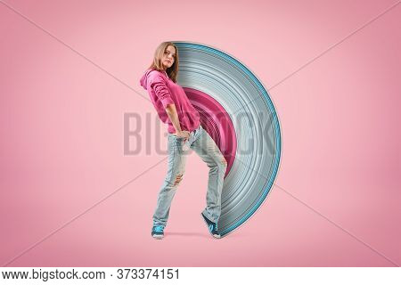 Young Confident Girl In Pink Hoodie And Light Blue Ripped Jeans Standing With Hand On Hip Looking At