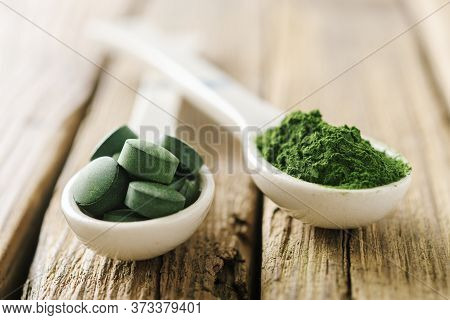 Two White Spoons With Pills And Chlorella Powder On Old Boards. Spoons With Chlorella Or Spirulina.