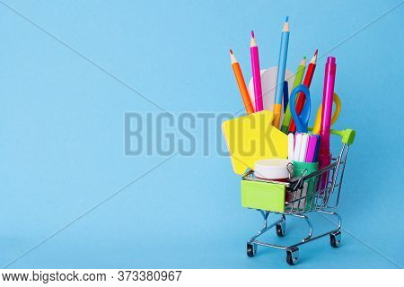 Bright Stationery Objects In A Mini Supermarket Trolley On A Blue Background. Back To School Concept