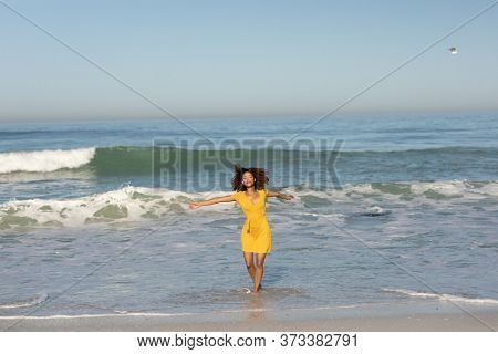 A happy, attractive mixed race woman with her arms outstretched enjoying free time on beach on a sunny day, wearing a yellow dress, walking, sun shining on her face. Relaxing summer vacation.