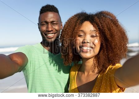A mixed race couple enjoying free time on beach on a sunny day together, taking a selfie, smiling and posing with sun shining on their faces. Relaxing summer vacation.