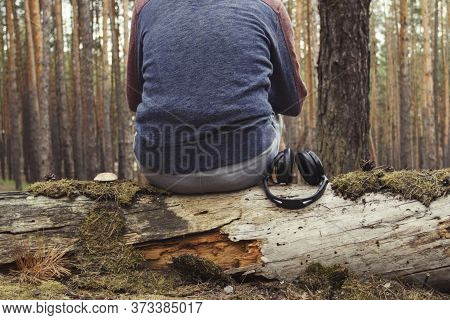 Man Sits On Fallen Tree With His Back To The Camera And Headphones Lie Down With Him In The Wild For