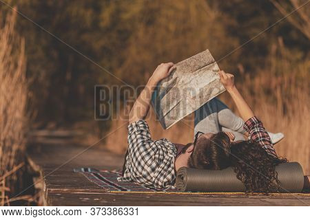 Beautiful Young Couple In Love Lying On A Picninc Blanket At Lake Docks, Reading A Map And Having Fu