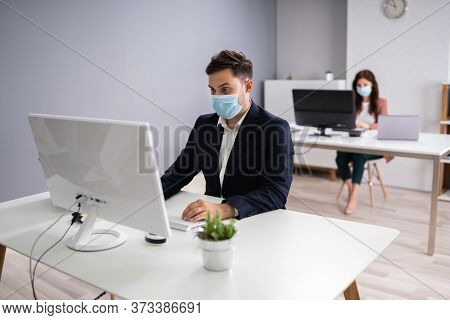 Business Employees In Office Wearing Medical Masks And Following Social Distancing Protocols
