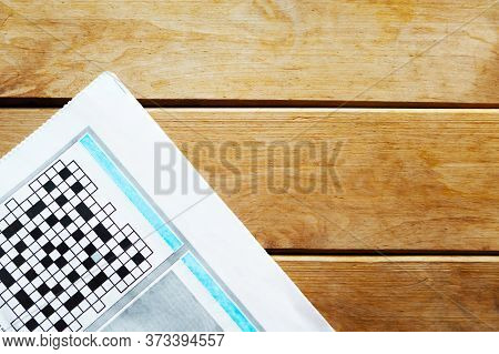 Newspaper With Crossword On Wooden Background. Copy Space For The Text