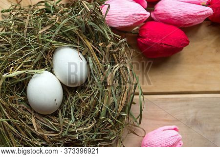 Eggs In Hay Nest And Tulips On Wooden Background. Easter Concept
