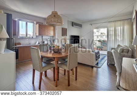 Open-concept Of A Kitchen, Dining Wooden Table And Living Room With Balcony In A Very Small Apartmen