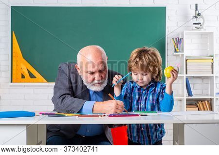 Elementary School. Senior Teacher In Classroom With Elementary School Kid. Professor And Pupil In Cl