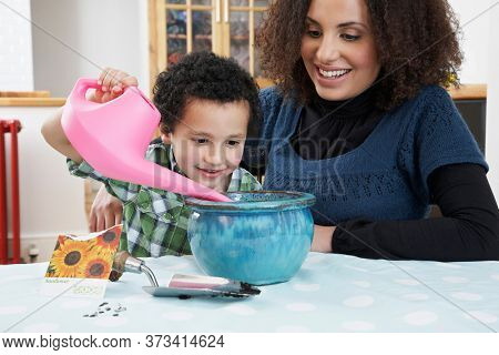 Mother assisting son (5-6) pouring water into flower pot