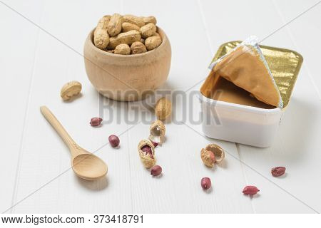 A Wooden Spoon, Peanut Paste, And A Bowl Of Peanuts On A White Wooden Table. Natural Peanut Cream.