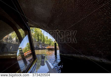 Amsterdam, Netherlands - July 02, 2018: Excursion On A Pleasure Boat Through The Canals Of Amsterdam